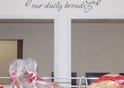 Give us this day our daily bread on wall with bread on racks